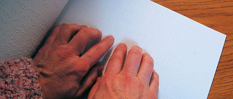 Person reading braille.